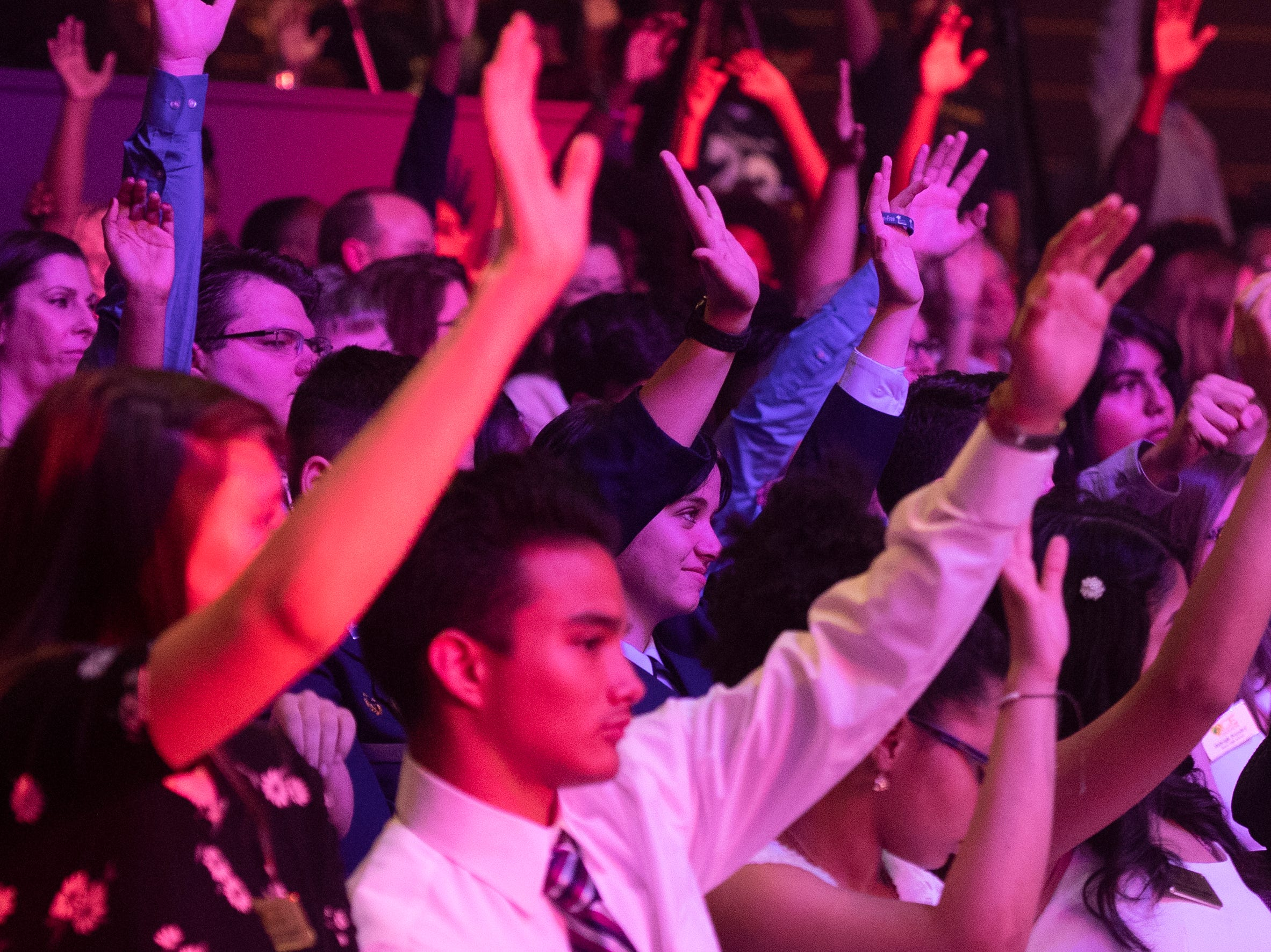 ACE award honorees raise their hands when asked questions about their futures during the keynote speech at the Coaches 4 Character ACE Awards held at Relentless Church Wednesday, May 15, 2019.