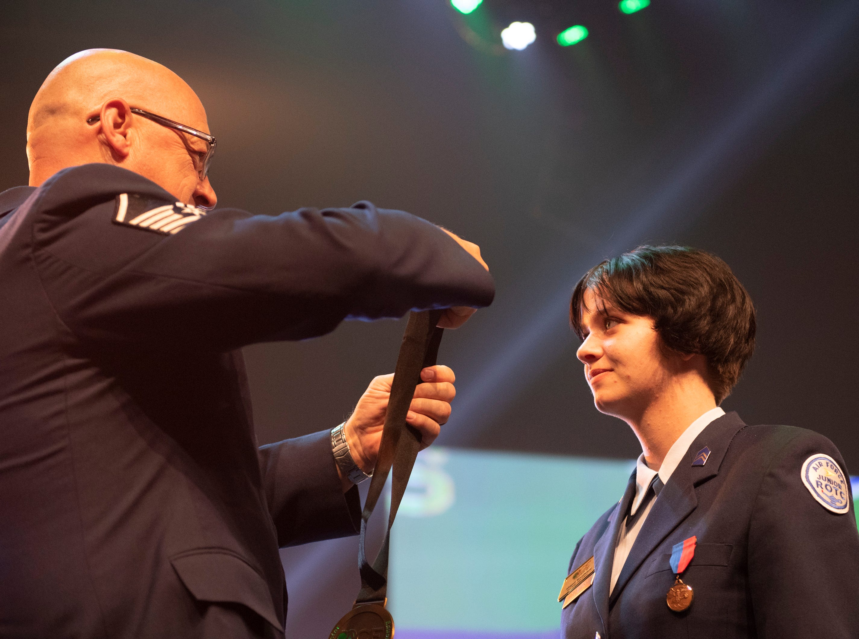 Abigail Woodward receives her ACE awards medal from Air Force JROTC instructor retired Master Sgt. Fred Fuller during the Coaches 4 Character ACE Awards held at Relentless Church Wednesday, May 15, 2019.