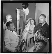 """Josh White back at Café Society Downtown in 1947. The article where this photo appeared says: """"His tremendous voice and masterful showmanship can keep any spot moving."""" Seen with him are stand-by Cliff Jackson, harpist Olivette Miller and the Gene Sedric band."""
