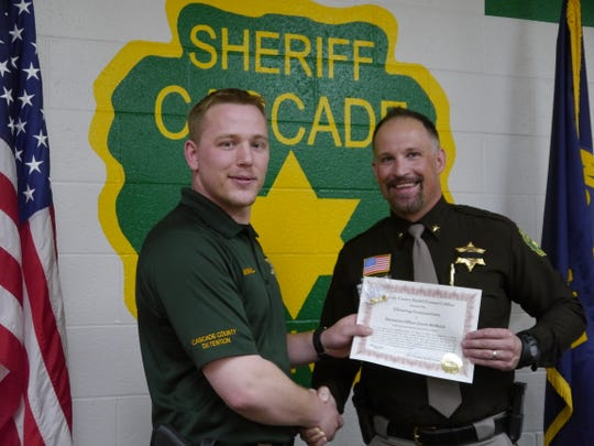 Detention officer Jacob McMahill, left, gets a handshake from Cascade County Sheriff Jesse Slaughter. McMahill likely saved a man's life after a vehicle crash in April.
