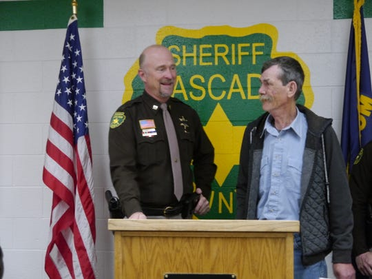 Cascade County Sheriff's Office Captain Scott Van Dyken, left, thanks civilian Russ Taylor, who helped evacuate his neighbors from a house fire south of Great Falls last August.