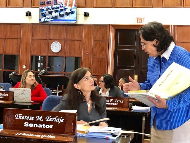Sen. Telo Taitague, right, confers with Sen. Therese Terlaje during a brief session break in this May 2019 file photo. Taitague, during a session on July 9, 2019, shares her concerns about charter school-related bills that were added on the session agenda.