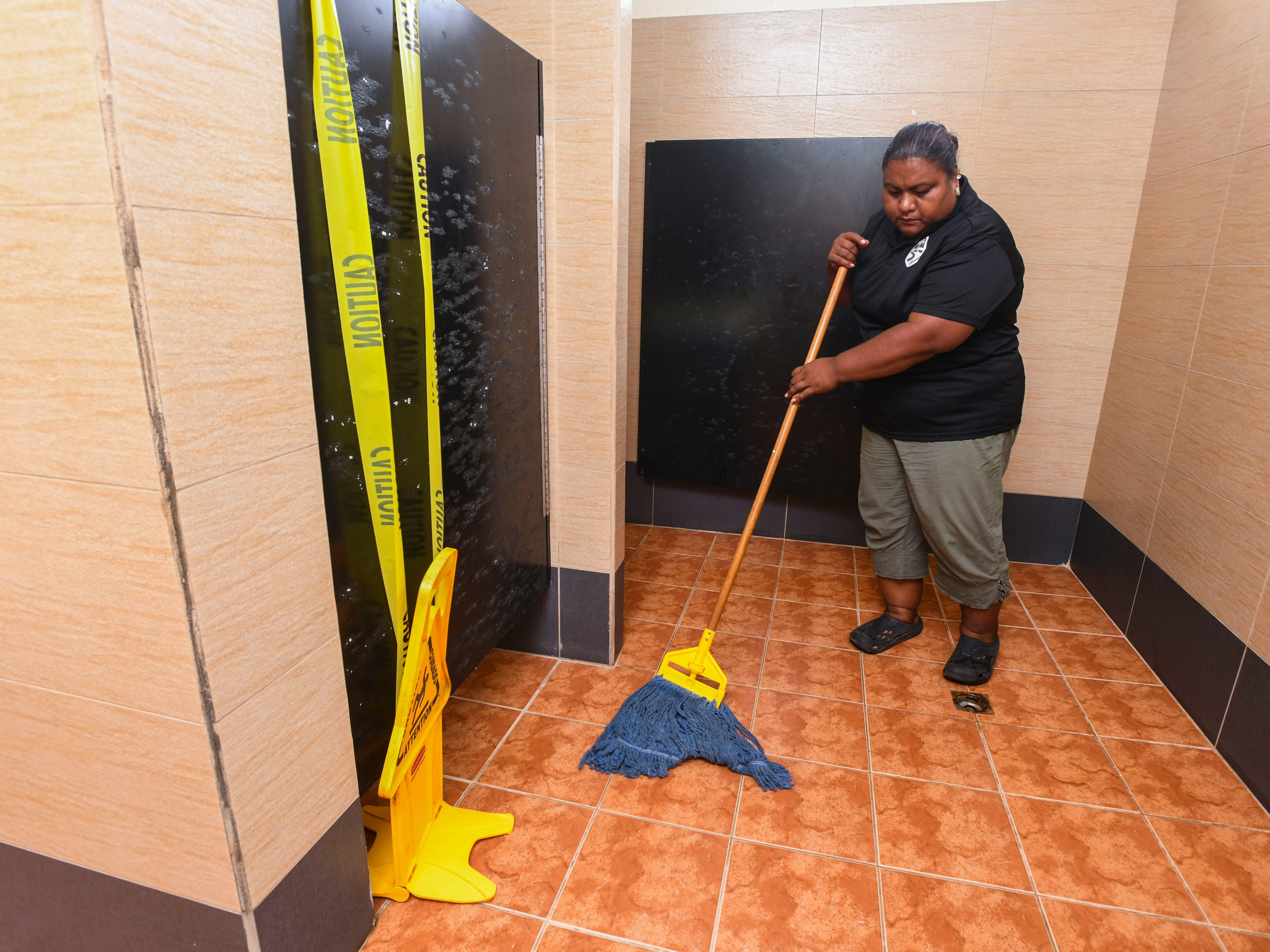 Yellow caution tape warns patrons of a non-working toilet stall as Dom's Maintenance worker Ren Esiel cleans within the women's restroom facility, near the Inarajan Natural Pools, on Thursday, May 16, 2019. Since May 1, the maintenance company has provided a worker to supply the restrooms and maintain the daily upkeep of the building from 9:00 a.m. to 5:00 p.m., said owner Dominic San Gil. But due to a minor plumbing issue, the stall was closed off until repairs can be performed by Department of Parks and Recreation personnel, San Gil added.
