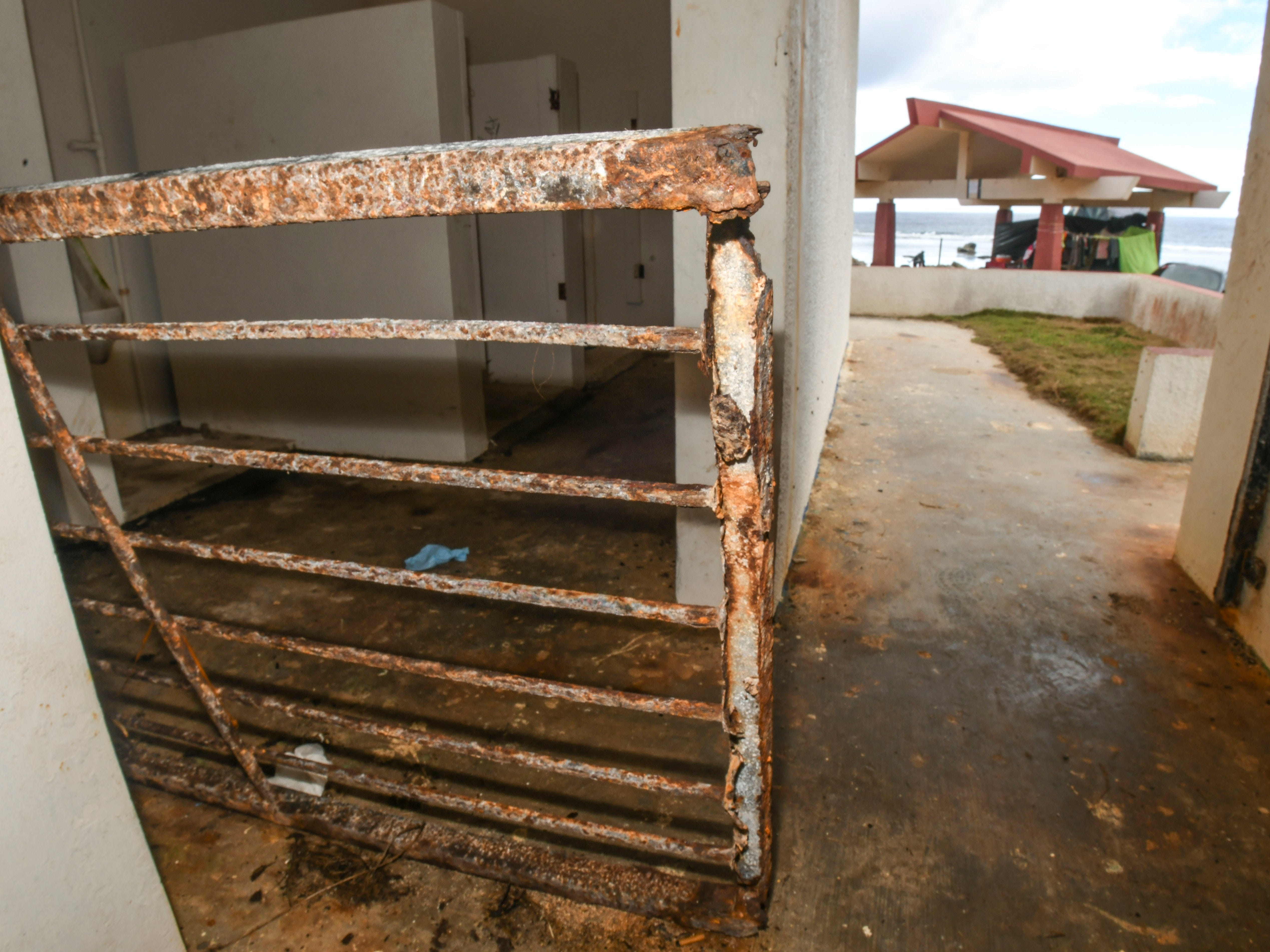 A rusted metal gate, that once served as a door for the men's restroom facility at Taga'chang Beach Park, can be found laying on its side against an interior wall, as men appearing to live in an open pavillion can be seen just outside, on Thursday, May 16, 2019.
