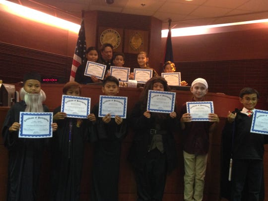 On May 8 the fifth grade GATE students from Captain H.B. Price Elementary School participated in the mock trial sponsored by the Judiciary of Guam. The students performed the trial of People vs Harry Potter. Pictured in front from left: Carl Carino as Professor Dumbledore, Francis Mondino as Ron Weasley, Joseph Payumo as Professor Snape, Dano Pangelinan as Rubeus Hagard, Robert O'Brien as Voldemort, and Taga Blas as Harry Potter. Back row from left: Alexis Gogue, defense attorney; Honorable Benjamin Sison; Misiah Murphy clerk and bailiff; Taelor Mafnas judge; and Savian Sablan prosecutor.