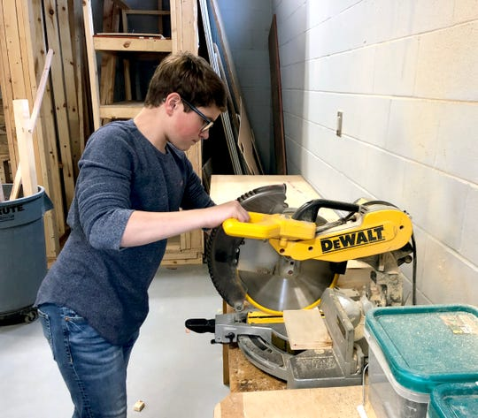 Sophomore Gabe Turner cuts a piece of wood to be used for a bereavement box.