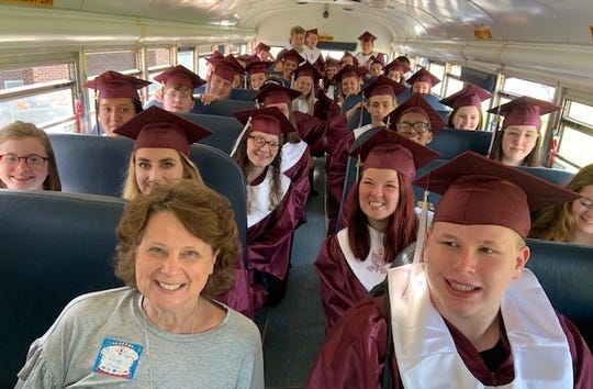 Niagara Elementary Principal Paige O'Nan, who is retiring after 24 years of school service, poses with former students as they show up for Thursday's Grad Walk on the last day of school.