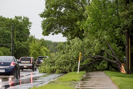 A fallen tree obstructs 86th street in front of North Central High School in Indianapolis on Thursday, May 16, 2019. Wind gusts as strong as 60 miles per hour left trees and power lines down across Indianapolis, and tens of thousands without power in Marion and Hamilton Counties.
