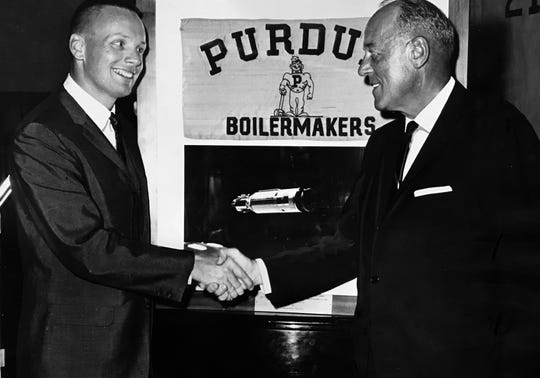 Astronaut Neil Armstrong (left) pilot of the FEmini-8 space craft and Purdue University graduate is shown with Purdue president Frederick L. Hovde with the Purdue banner which Armstrong borrowed from the university to take to on the orbital voyage. May 1, 1966.