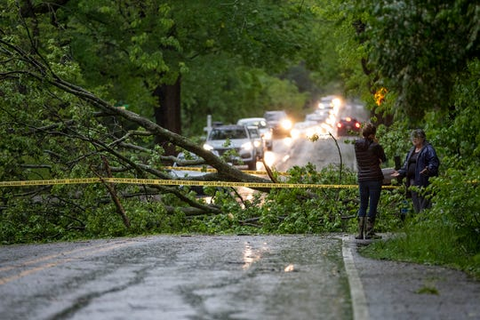 A fallen tree obstructs East 80th Street near the intersection with North Evanston Road in Indianapolis on May 16, 2019.