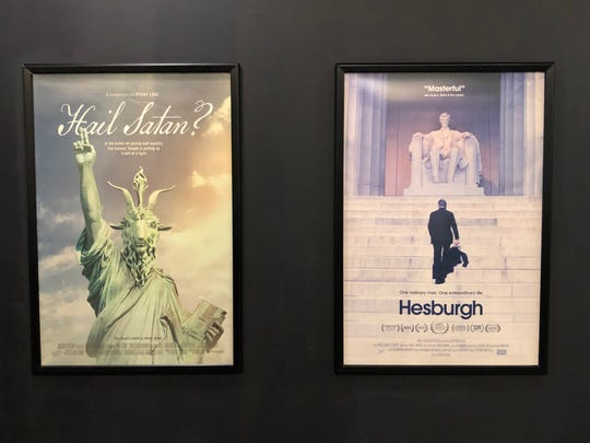 """Films """"Hesburgh"""" and """"Hail Satan?"""" will both have their FilmScene premier on Friday, May 17. The posters hang next to each other in FilmScene's lobby."""