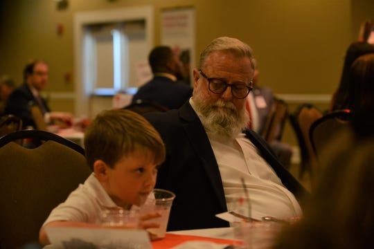 Fallen paramedic Zachary Pruitt's father Roger Pruitt looks at Zachary's son Rylan Pruitt, as Zachary Pruitt's posthumous Uniformed Hero of the Year award rests on the table in front of them at the 2019 Red Cross Heroes Luncheon at Union University on Thursday.