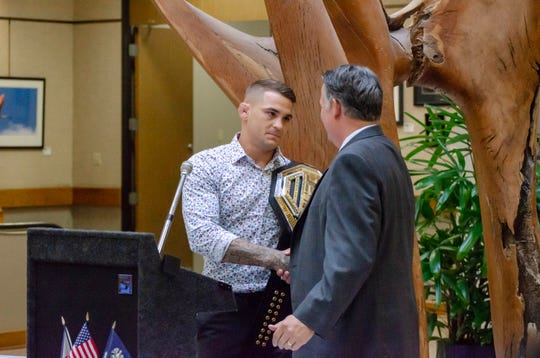 Lafayette Mayor-President Joel Robideaux (right) awards UFC lightweight champion Dustin Poirier a key to the city for his work with the Good Fight Foundation and his contributions to the community.
