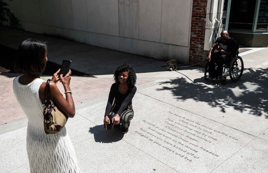 La'Shay Todd takes a photo of daughter Alazhia Mobley with her street poem 'You Have to Push the Clouds' that's enscribed on the sidewalk along Fourth Street in downtown Louisville.