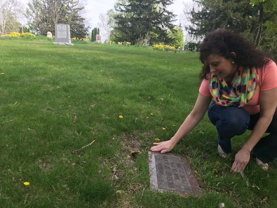Michelle Pohl of Portland clears debris from the marker of her great uncle Richard McKimmy. McKimmy died in 1926 at the Boys Training School in Lansing. An effort is underway to mark the graves of 60 other youths.