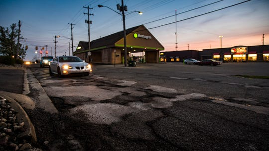 Vehicles maneuver around a cluster of potholes Wednesday, May 15, 2019 on Clippert Street between East Grand River Avenue and Saginaw Road just north of Frandor Shopping Center.