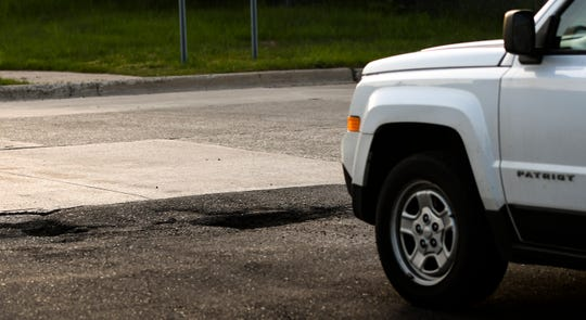 A vehicle nears two large potholes at the corner of Sellers Avenue and North Homer Street, Wednesday evening, May 15, 2019.