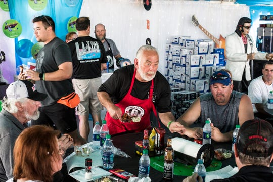 Mike Pittman hands out barbecue inside of the Curly Tail Smokers tent during the Kingsford Tour of Champions on Thursday.