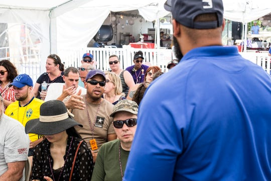 Michael Blue asks a question during the tour of The Pork University tent during the Kingsford Tour of Champions on Thursday.