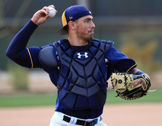 Milwaukee Brewers catcher Jacob Nottingham throws to first base during spring training drills in Phoenix.