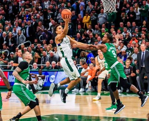 89ac241c21 Milwaukee Bucks guard Malcolm Brogdon shoots between Boston Celtics guard  Brad Wanamaker and Boston Celtics forward