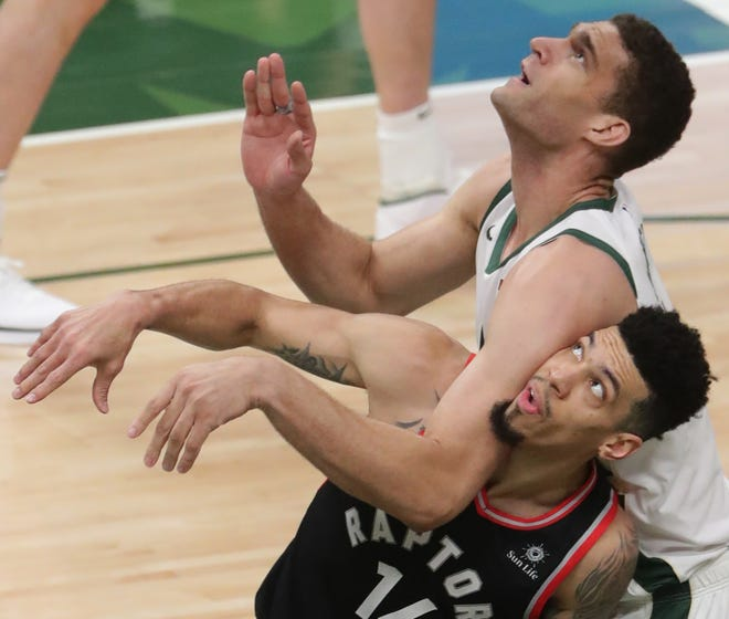 Toronto Raptors guard Danny Green (14) feels the pressure from center Brook Lopez (11) while waiting for a rebound  during the first half of their Eastern Conference finals game Wednesday, May 15, 2019 at Fiserv Forum in Milwaukee, Wis.