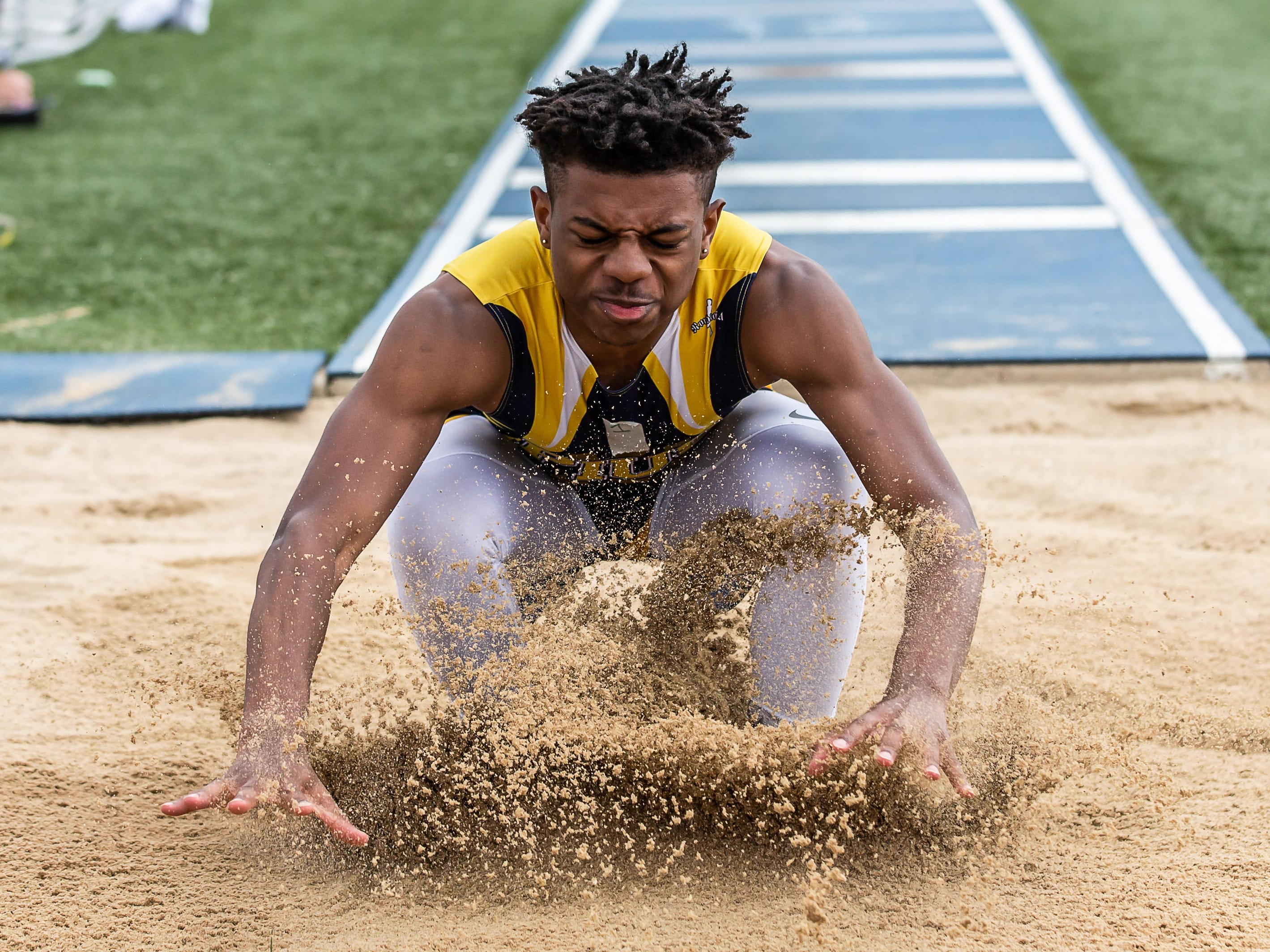 Pius Xi's Maurice Hughes, jr. competes in the long jump at the Woodland Conference Track and Field Championships in West Allis on Tuesday, May 14, 2019.
