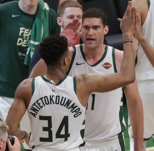 Milwaukee Bucks center Brook Lopez (11) congratulates forward Giannis Antetokounmpo (34) after half of their Eastern Conference finals game Wednesday, May 15, 2019 at Fiserv Forum in Milwaukee, Wis. The Milwaukee Bucks beat the Toronto Raptors 108-100.