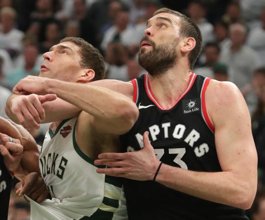 Bucks center Brook Lopez and Raptors center Marc Gasol get tangled up during a free throw in Game 1 at Fiserv Forum.