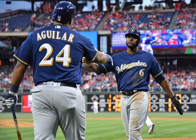 Brewers centerfielder Lorenzo Cain celebrates with first baseman Jesus Aguilar after scoring in the third inning Wednesday night.