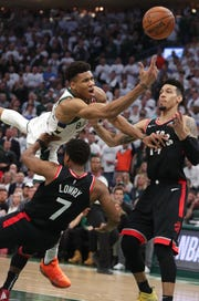 Bucks forward Giannis Antetokounmpo draws a foul on Raptors guard Kyle Lowry in the second half Wednesday night at Fiserv Forum.