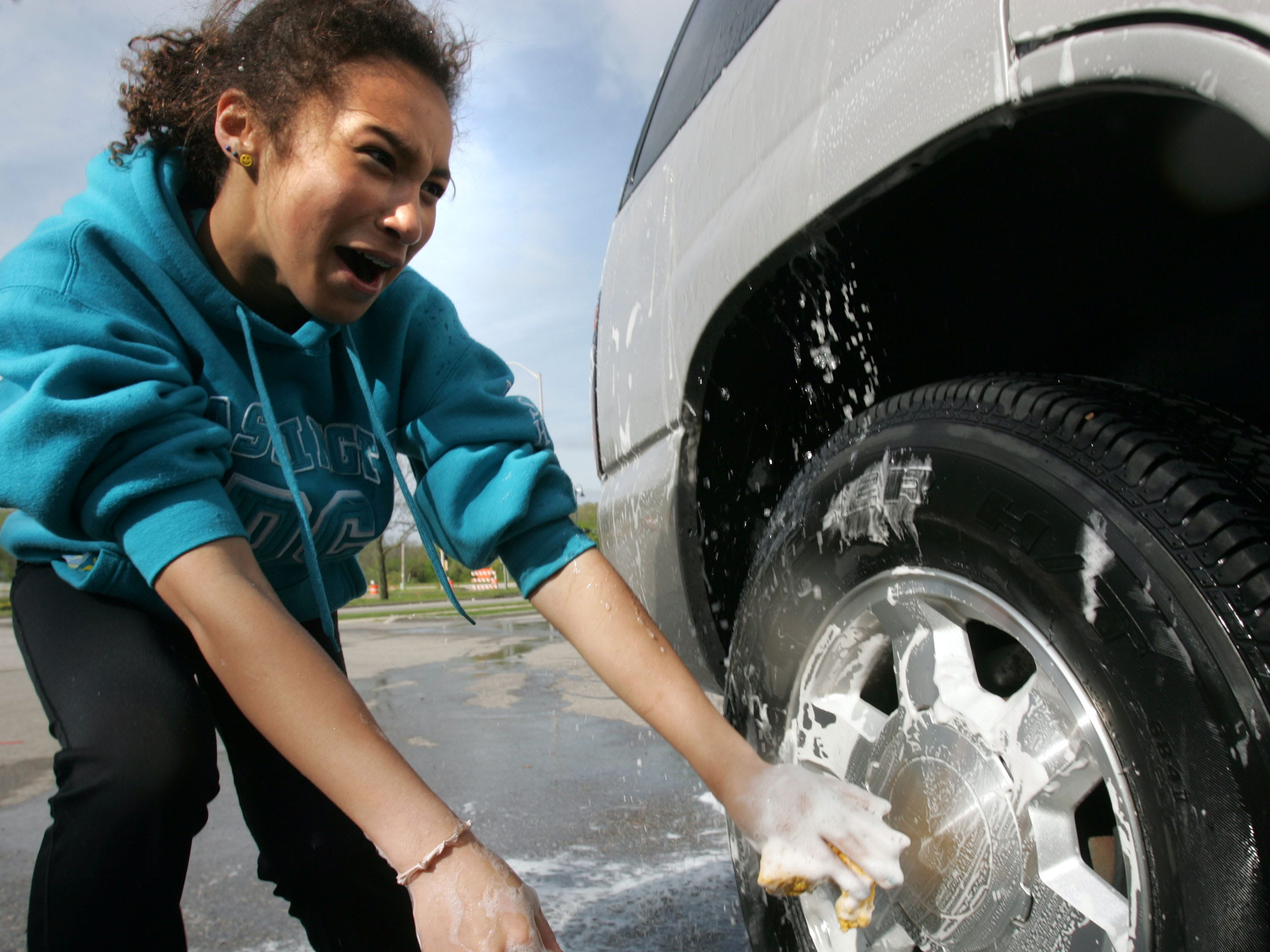Peri Sem, 14, reacts as she is inadvertently sprayed with water while washing a car in the parking lot of a Speedway gas station May 16, 2009, in Greendale. Peri was taking part in a fundraiser to raise money for a student trip to China with the People to People Student Ambassador program.