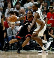 The Raptors' Kawhi Leonard tries to dribble around the Bucks'  Khris Middleton in Game 1.