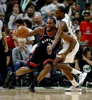The Raptors' Kawhi Leonard tries to dribble around the Bucks'  Khris Middleton in Game 1.