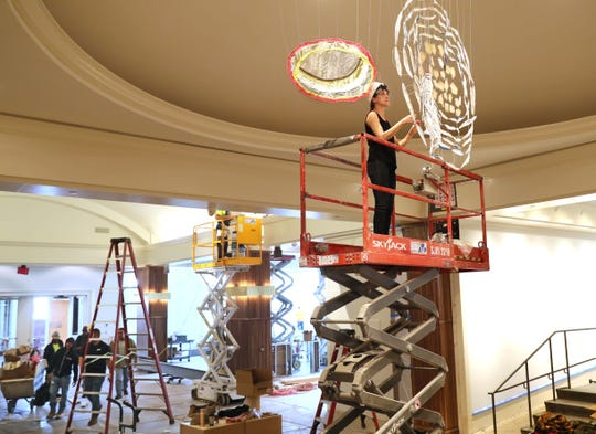 "Artist Caroline Lathan-Stiefel works on the installation of her art Thursday at the Saint Kate hotel. Lathan-Stiefel creates large-scale, site-specific installations using fabric, pipe cleaner, wire, thread, fishing weights and plastic. She said she considers these installations to be ""drawings-in-space."""