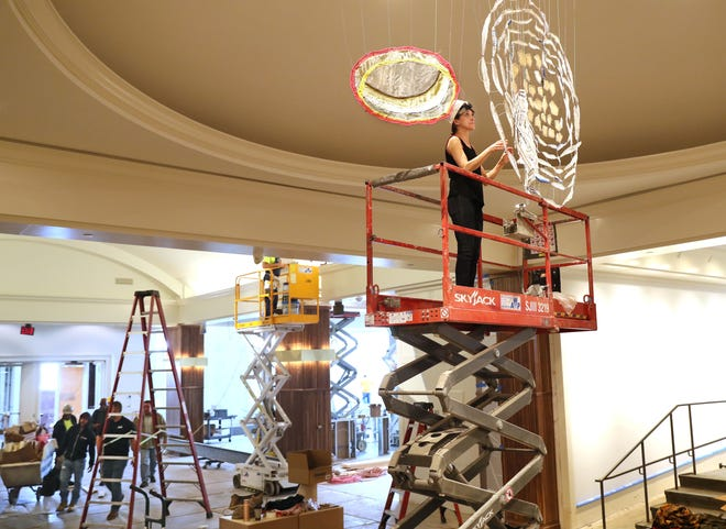 """Artist Caroline Lathan-Stiefel works on the installation of her art Thursday at the Saint Kate hotel. Lathan-Stiefel creates large-scale, site-specific installations using fabric, pipe cleaner, wire, thread, fishing weights and plastic. She said she considers these installations to be """"drawings-in-space."""""""