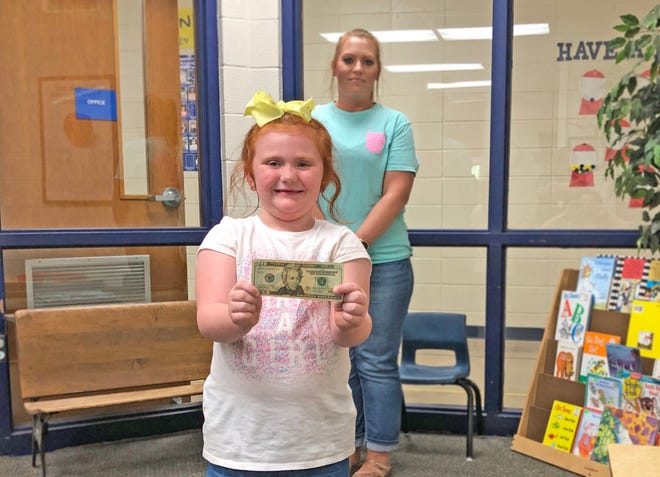 Kindergarten student Sophia Powell illustrates the cost of school supplies through the district's bulk ordering program while her mother, Sherri Powell, looks on.