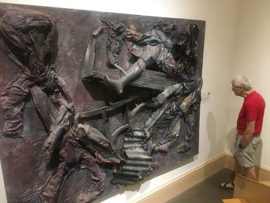 A guest examines Thornton Dial Sr.'s Lost Americans at the Montgomery Museum of Fine Arts on Tuesday, May 14, 2019.