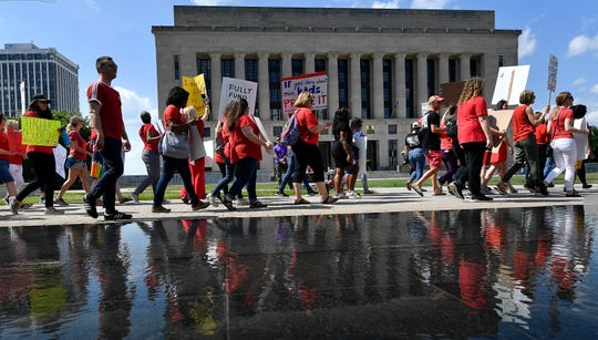Teachers and supporters march from Cumberland Park to the Metro Courthouse demanding higher wages Thursday, May 16, 2019 in Nashville, Tenn.