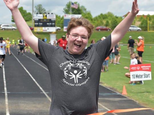 Youth celebrates 2019 Special Olympics win.