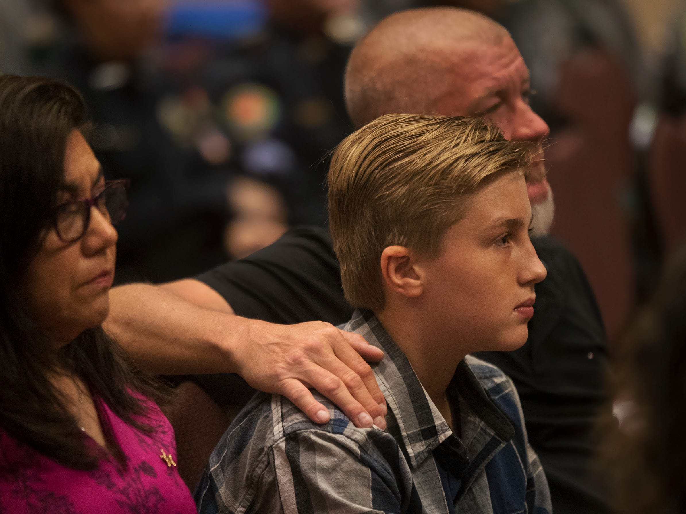 Zackary Gibbons, 13, is comforted by his father, Lindell Brian Gibbons, during a law enforcement memorial honoring Zackary's grandfather, Lindell J. Gibbons and other local officers killed in the line of duty on Wednesday at East Naples United Methodist Church. Thirteen officers have been killed in Collier County since 1928.