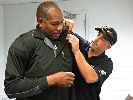 Atlantic League umpire Calvin Baker getting fitted with an earpiece and transponder by an MLB official on Thursday, May 16, 2019 before the Somerset Patriots take on the High Point Rockers in Bridgewater, NJ.