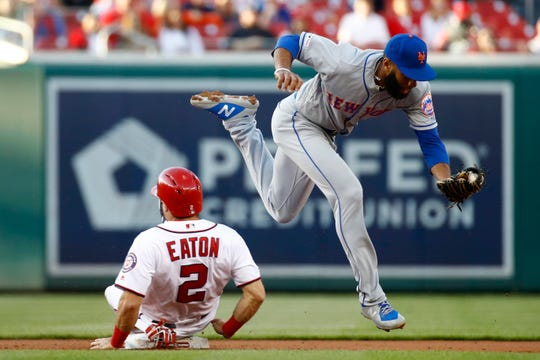 Washington Nationals' Adam Eaton, left, slides safely into second base as New York Mets shortstop Amed Rosario is unable to attempt a double play on a bunt by Victor Robles in the first inning of a baseball game, Wednesday, May 15, 2019, in Washington. (AP Photo/Patrick Semansky)