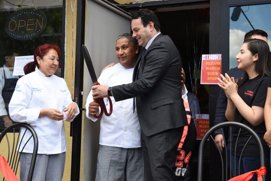 Husband and wife Juana Rivas and Marco Rivero, Mayor Andre Sayegh, and their daughter Estephanie Rivero celebrate after cutting the ribbon on Wasiyki. The husband and wife, graduates of Eva's culinary school opened their new restaurant on Main St. in Paterson on Thursday, May 16, 2019.
