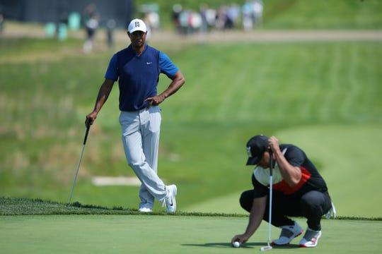 May 16, 2019; Bethpage, NY, USA; Brooks Koepka lines up his putt on the 18th green as Tiger Woods looks on during the first round of the PGA Championship golf tournament at Bethpage State Park - Black Course.