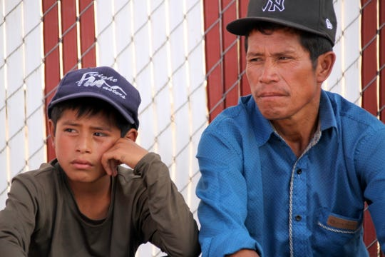 Guatemalan father and son, Felipe Perez Pablo, and Felipe Perez Andres, 12, sit at the Mimbres Food Mart waiting to board a bus for Tennessee on Wednesday..