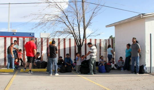 A group of approximately 20 immigrants wait outside of Mimbres Food Mart for the Greyhound bus to roll in.