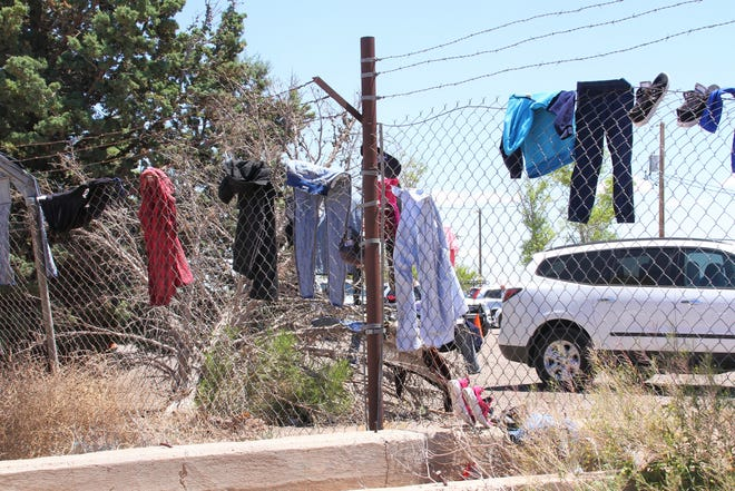 Clothing items of immigrants hang along Southwestern New Mexico State Fairgrounds' fencing.