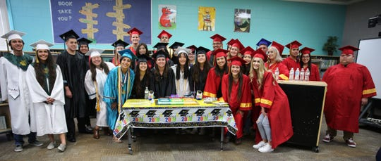 A group of graduating Las Cruces Public School students pose next to a cake, Thursday May 16, 2019 at Hillrise Elementary School, after their senior walk.