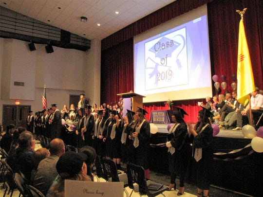 Graduates from Vista Nueva High School stand up during their   commencement ceremony on May 15 in the Aztec High School multi-purpose room.
